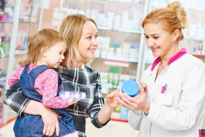 pharmacist woman demonstrating vitamin to child girl with mother