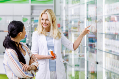 pharmacist holding containers with medication and consulting customer in drugstore